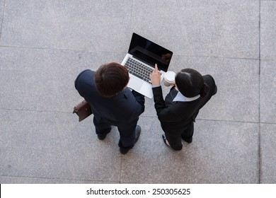 Business team working on laptop, view from the top
