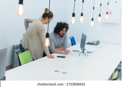 Business team working on new project and smiling. Man and woman sitting together in modern office for project discussion.