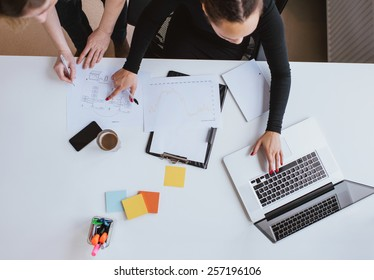 Business team working on a new plan with laptop. Top view of two young women executives working together with laptop and taking notes.