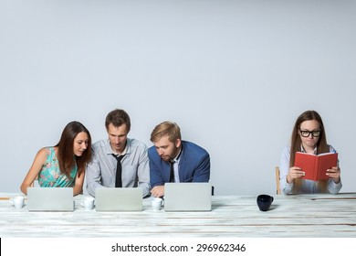 Business team working together at office on light gray background. all working on laptops. boss reading notebook. copyspace image