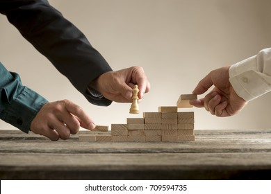 Business teamwork concept with a businessman moving a chess piece queen up a series of steps formed by blocks being put in place by his team.