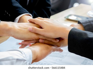 Business teamwork concept with hands of businessmen and businesswomen together above office table