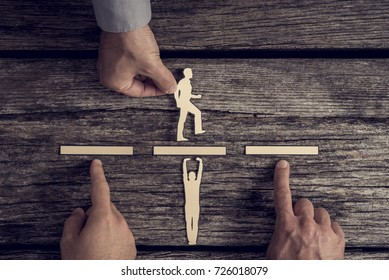 Business teamwork concept with the hands of three businesspeople supporting or assisting paper cut outs of two men over rustic wood with copy space.
