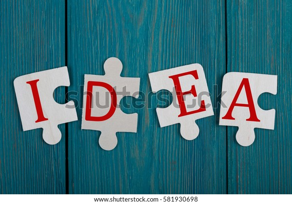 """Business Teamwork Concept - Jigsaw Puzzle Pieces with text """"IDEA"""" on blue wooden background"""