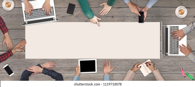 Business Teamwork concept - top view of eight business people. White blank sheet of paper in the middle of the wooden table.