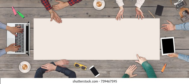 Business Teamwork concept - top view of six business people. White blank sheet of paper in the middle of the wooden table.