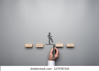 Business teamwork and cooperation concept - silhouette of a businessman walking across wooden pegs with other businessman drawing the missing step for his colleague.