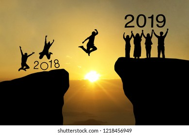 Business teamwork hands up and jump to the beautiful golden sky from text 2018 to text 2019 background .The concept of business sucess,victory,achieve target goal,busness growth.