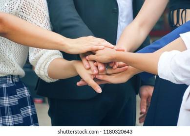 Business teamwork holding hands together.