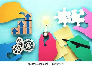 Business teamwork and innovation concept. Colorful hands silhouettes holding lightbulb, puzzle pieces, pen, wood blocks and gears on blue background.