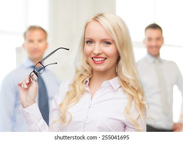 business, teamwork and people concept - smiling businesswoman, student or secretary with eyeglasses over office and group of colleagues background