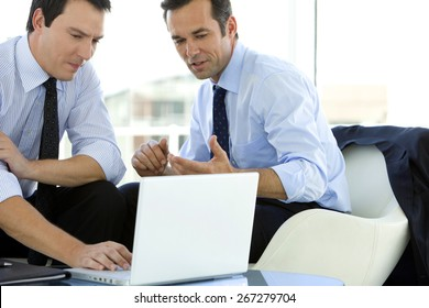 Business teamwork - two corporate businessmen working together on laptop