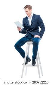Business and technology. Attractive young man using table computer while sitting on chair. Isolated on white.