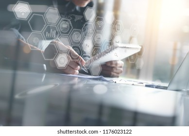 Business and technology, BI Business Intelligence concept. Businessman working on laptop computer, digital tablet at modern office with computer icons, IoT Internet of Things interface