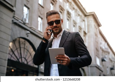 Business. Technology. City walk. Handsome businessman is talking on the mobile phone, using a tablet and smiling while walking outdoors