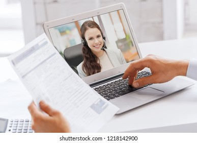 business, technology and communication concept - close up of businessman with laptop computer having video call with customer service operator, partner or secretary at office