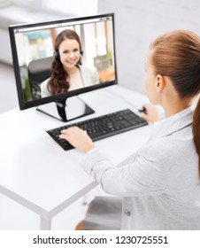 business, technology and communication concept - close up of businesswoman with pc computer having video call with customer service operator at office