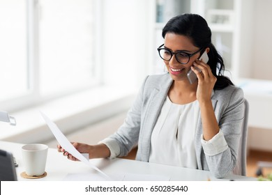 business, technology, communication and people concept - happy smiling businesswoman with papers calling on smartphone at office