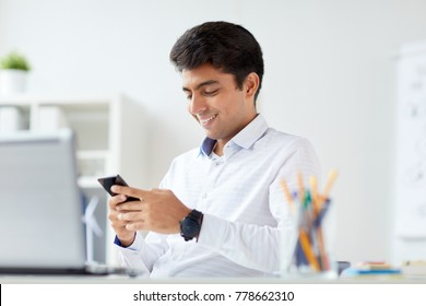 business, technology, communication and people concept - happy businessman with smartphone at office