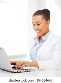 business and technology concept - african businesswoman with laptop in office