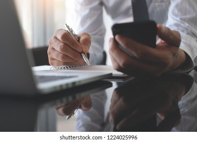 Business and technology concept. Businessman or student working on laptop computer, using smart mobile phone and writing with pen on notebook in office, close up