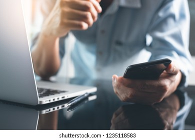 Geschäfts- und Technologiekonzept. Pensive Geschäftsleute, Freiberufler, Programmierer, die Smartphone verwenden, während sie am Laptop arbeiten, denken Sie an sein Projekt im modernen Büro, Nahaufnahme