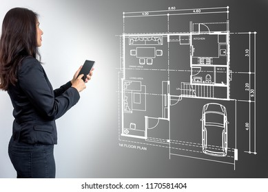 Business technology &  internet concept - Businesswoman (Architect - Interior designer) using smartphone, working with home lay-out plan on futuristic virtual screen