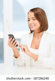 business, technology and internet concept - smiling businesswoman browsing in smartphone in office