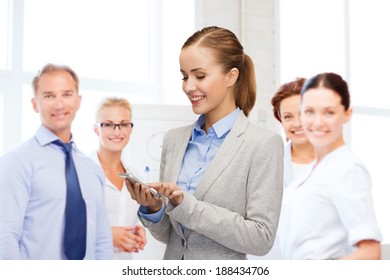 business, technology, internet and education concept - friendly young smiling businesswoman with smartphone