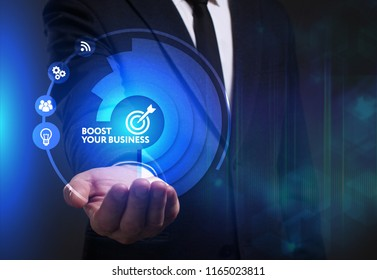 Business, Technology, Internet and network concept. Young businessman working on a virtual screen of the future and sees the inscription: Boost your business