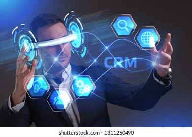 Business, Technology, Internet and network concept. Young businessman working in virtual reality glasses sees the inscription: CRM