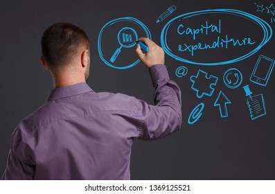 Business, Technology, Internet and network concept. A young businessman writes on the blackboard the word: Capital expenditure
