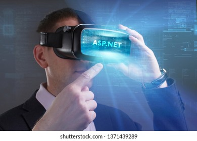 Business, Technology, Internet and network concept. Young businessman working in virtual reality glasses sees the inscription: ASP.NET