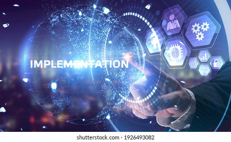 Business, Technology, Internet and network concept. Young businessman working on a virtual screen of the future and sees the inscription: Implementation