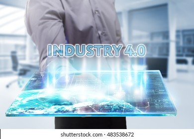 Business, Technology, Internet and network concept. Young businessman working on a tablet of the future, he sees the inscription: industry 4.0