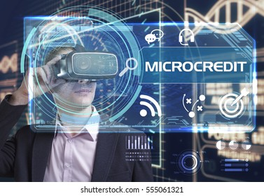 Business, Technology, Internet and network concept. Young businessman working in virtual reality glasses sees the inscription: microcredit