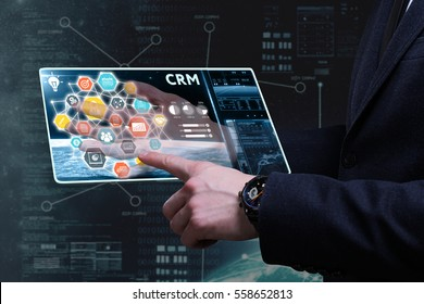 Business, Technology, Internet and network concept. Young businessman working on a tablet of the future, he sees the inscription: CRM