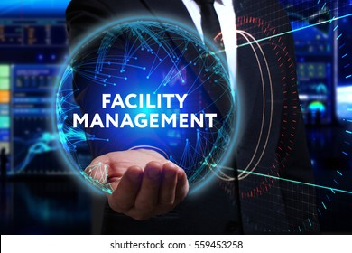 Business, Technology, Internet and network concept. Young businessman working in the field of the future, he sees the inscription: facility management