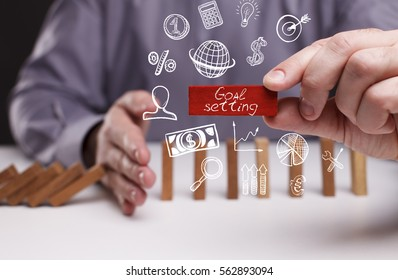 Business, Technology, Internet and network concept. Young businessman shows the word: Goal setting