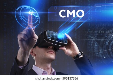 Business, Technology, Internet and network concept. Young businessman working in virtual reality glasses sees the inscription: CMO