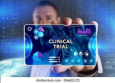 Business, Technology, Internet and network concept. Young businessman showing a word in a virtual tablet of the future: Clinical trial