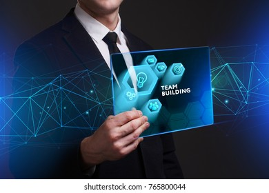 Business, Technology, Internet and network concept. Young businessman working on a virtual screen of the future and sees the inscription: Team building