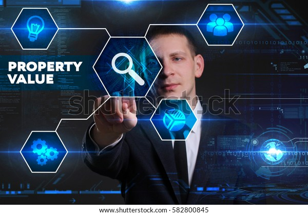 Business, Technology, Internet and network concept. Young businessman working on a virtual blackboard of the future, he sees the inscription: property value