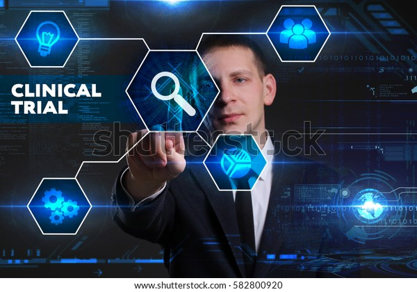 Business, Technology, Internet and network concept. Young businessman working on a virtual blackboard of the future, he sees the inscription: clinical trial