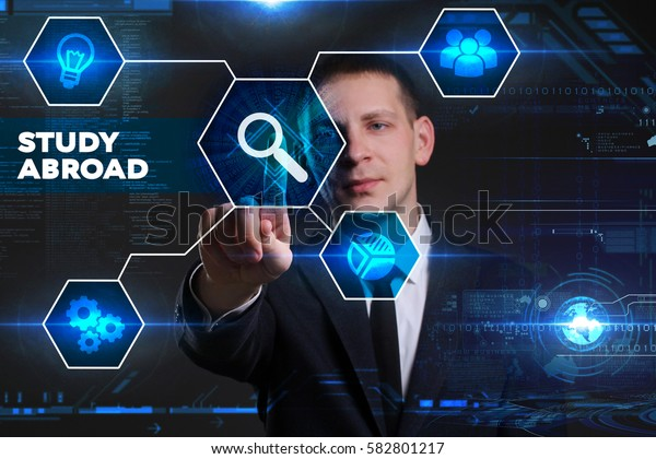 Business, Technology, Internet and network concept. Young businessman working on a virtual blackboard of the future, he sees the inscription: study abroad
