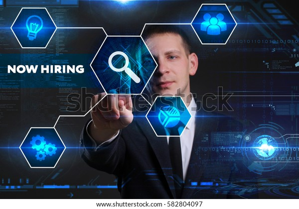 Business, Technology, Internet and network concept. Young businessman working on a virtual blackboard of the future, he sees the inscription: now hiring