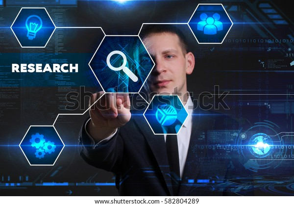 Business, Technology, Internet and network concept. Young businessman working on a virtual blackboard of the future, he sees the inscription: research
