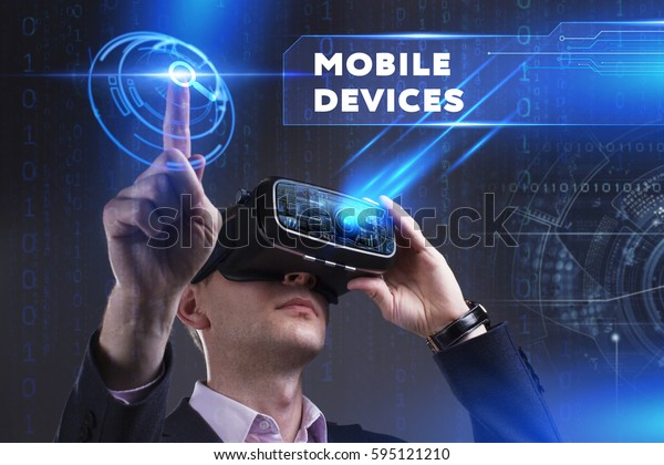 Business, Technology, Internet and network concept. Young businessman working in virtual reality glasses sees the inscription: Mobile devices