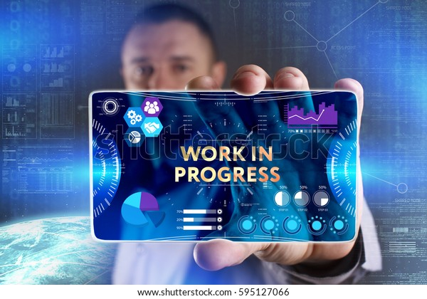 Business, Technology, Internet and network concept. Young businessman showing a word in a virtual tablet of the future: Work in progress