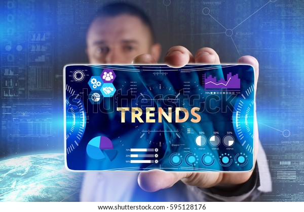 Business, Technology, Internet and network concept. Young businessman showing a word in a virtual tablet of the future: Trends